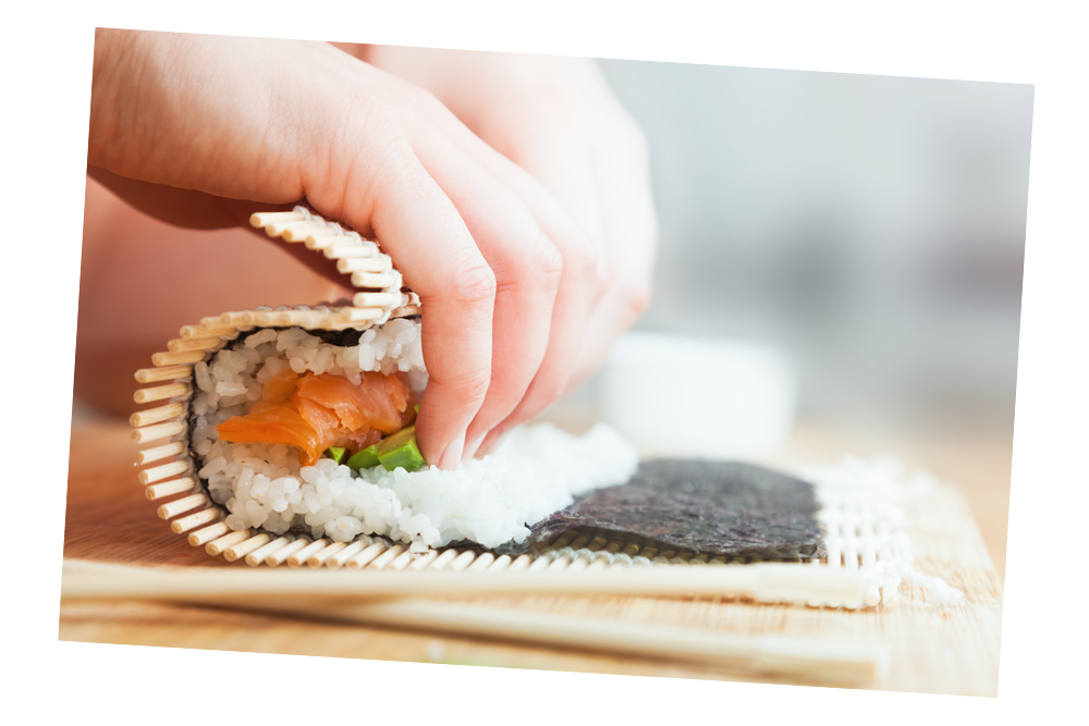 Hands rolling sushi